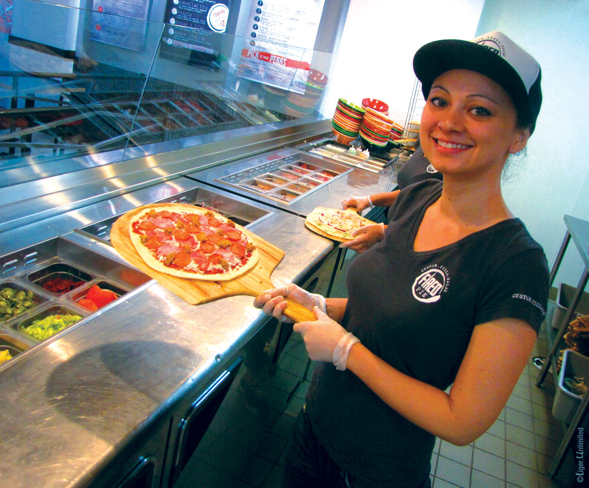 girl holding fired pie pizza