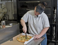 the photo shows a pizzeria employee practicing phone etiquette while slicing a pizza