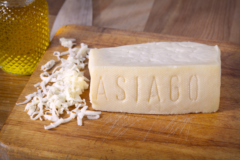 this photo depicts Asiago to illustrate the different types of hard cheeses that can be used for pizzas.
