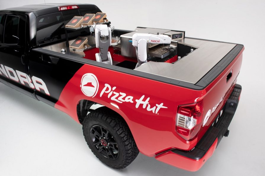 this photo shows a pizza robot on a Pizza Hut delivery truck