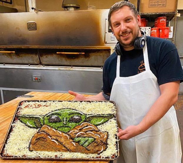 this photo shows Eric Palmieri with his pizza art, a Baby Yoda pizza