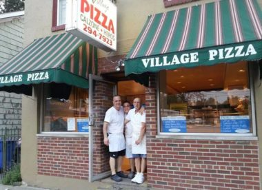 this photo shows the owners of Village Pizza, which lets customers eat now and pay later during the coronavirus crisis