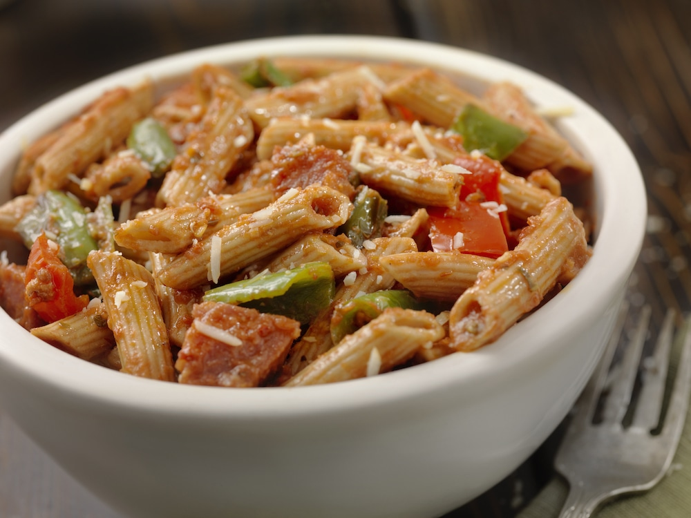 this photo shows a tasty-looking bowl of gluten-free penne pasta with sausage and peppers