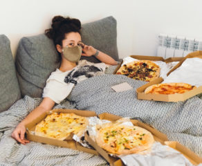 this photo shows a woman wearing a COVID-19 mask while eating pizza at home