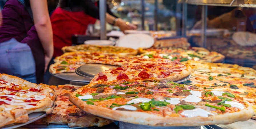 this photo shows a variety of Italian pizzas in a shop display with kitchen workers arranging the pizzas.