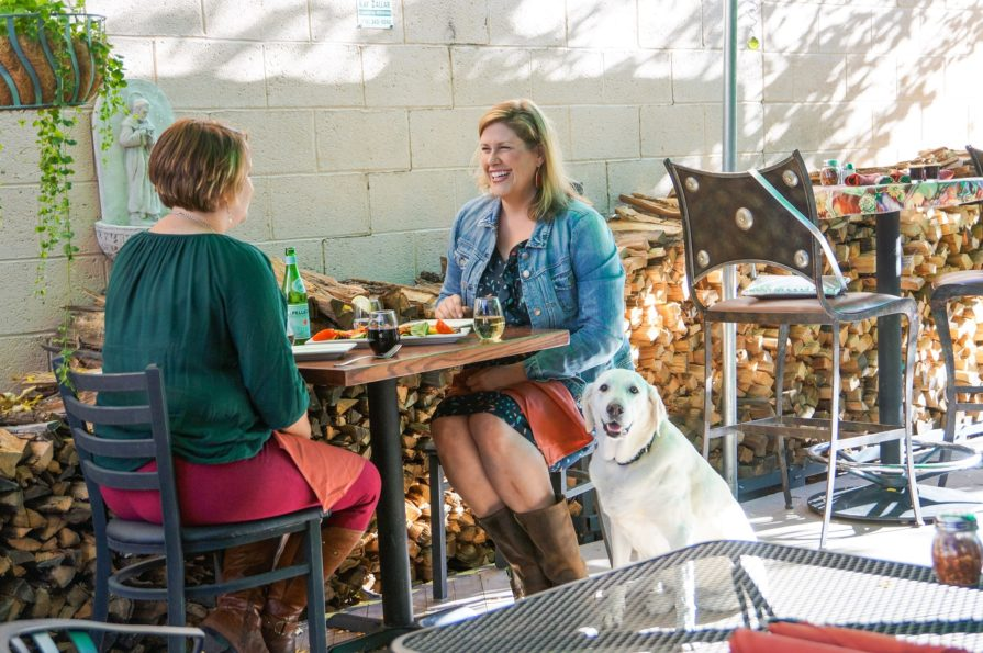 this photos shows two women dining outdoors at Pizzeria Rustica