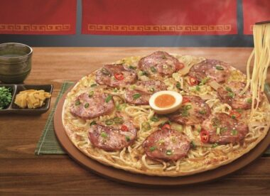 this photo shows a ramen pizza from Pizza Hut Taiwan with a soft boiled egg in the center and ramen noodles for topping