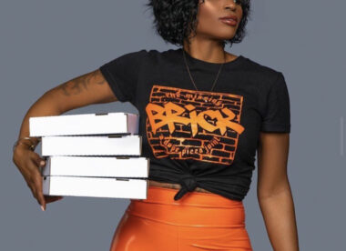 this photo shows Que Wimberly in a Missing Brick t-shirt holding several pizza boxes