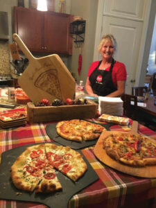 this photo shows chef and caterer Gail Churinetz with some of the many specialty pizzas she can make for a pizza party in Memphis