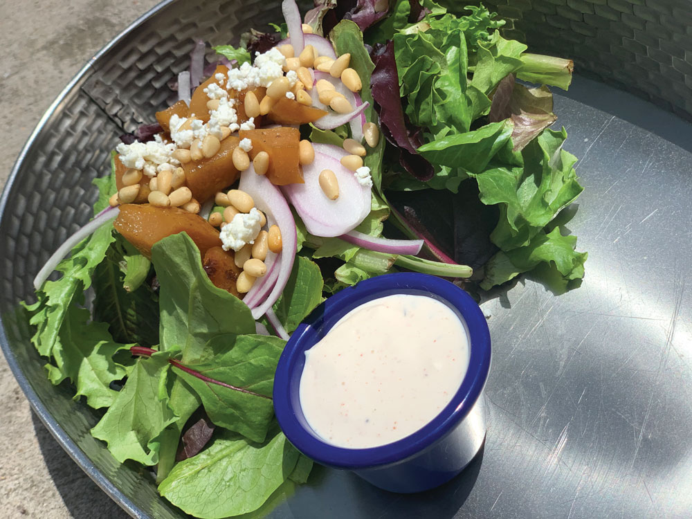 this photo from Hops Pie shows a popular vegan ranch dressing in a blue cup with a salad next to it