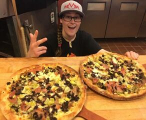 an employee shows off two wood-fired pizzas from Pizzeria Caldera, which has stopped offering plastic straws