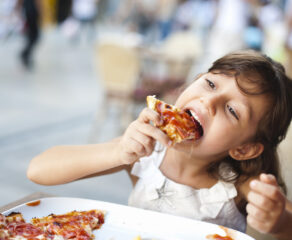 this photo of a little girl eating pizza illustrates increased customer satisfaction with chains like Domino's and Pizza Hut during the pandemic.