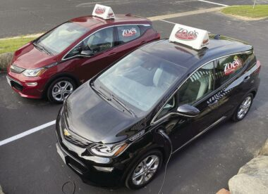 this photo shows a pair of electric vehicles, both Chevy Bolts, used by Zoe's Pizzeria for pizza delivery