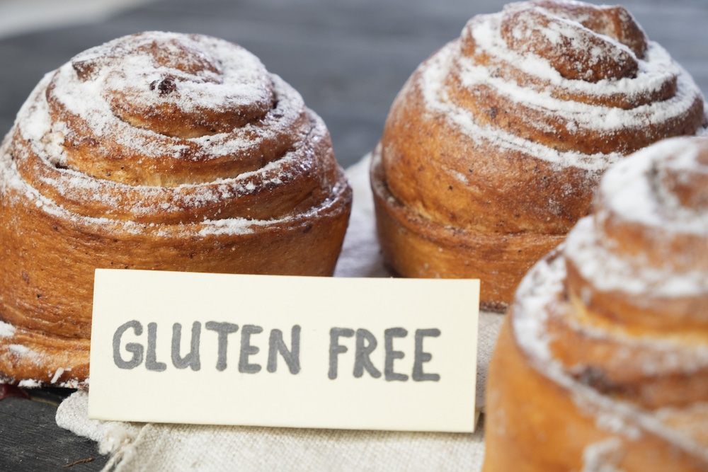 "this photo shows several gluten-free pastries arrayed in a tasteful display with a sign that reads ""gluten-free"""