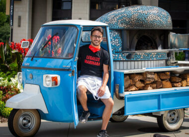 this photo shows Alessio Lacco in a blue three-wheeled Vespa scooter used by Atlanta Pizza Truck
