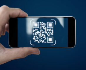 this photo shows a hand holding a phone with a QR code on the screen