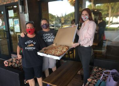 this photo shows Phoebe and Jennifer Morales-Siegel, owners of Pizza Girls, giving a Hawaiian pizza to Amy Siegel Oran