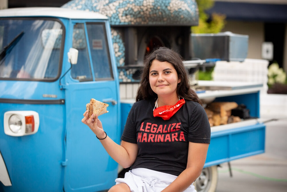 this photo shows Sofia Arango eating a slice in front of Atlanta Pizza Truck