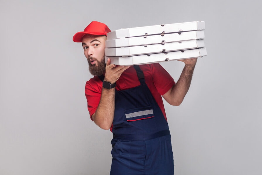 this photo depicts a third-party delivery employee delivering a pizza