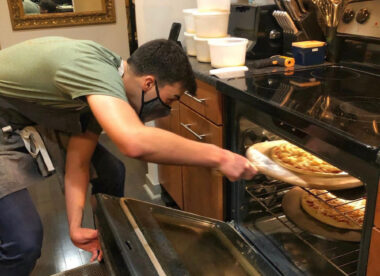 this photo shows Ben Berman of Good Pizza checking a pizza in his oven