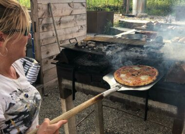 this photo shows Megan Jones-Holt, aka the Pizza Witch, putting a pizza in the oven at Market Pizza in Stockton, New Jersey