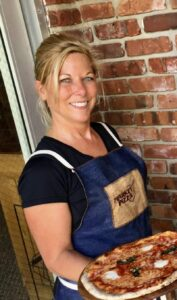 this photo shows Pizza Witch Megan Jones-Holt holding up one of her specialty pizzas at Pizza Market.
