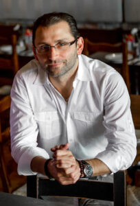 this is a photo of Tony D'Aiuto of Stella Hospitality Group in a white shirt and wearing glasses