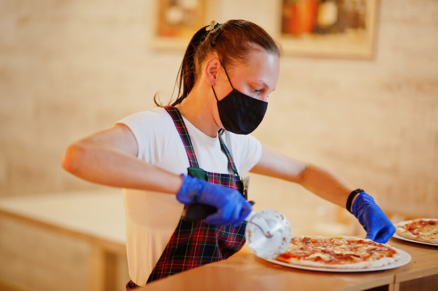 this photo of a woman slicing a pizza shows a restaurant worker who would be affected by an increase of the minimum wage