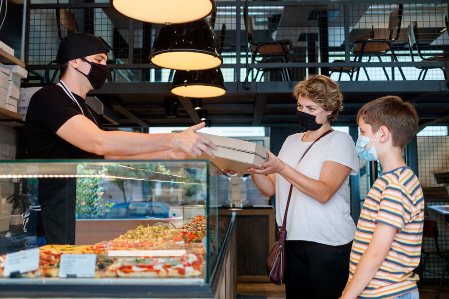 this photo shows two people taking carryout pizza in a pizzeria to illustrate the link between COVID-19 and indoor dining