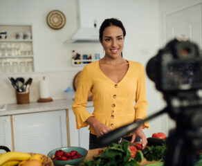 this photo shows a woman creating a recipe video as part of her restaurant's YouTube marketing strategy