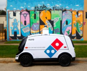 this photo shows Domino's self-driving pizza delivery car in front of a bright Houston, Texas mural