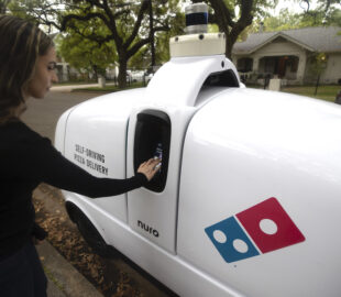 this photo shows a customer retrieving an order from Domino's self-driving delivery car
