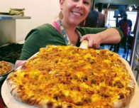 this photo shows the owner of Pleasant Grove Pizza Farm with a delicious-looking pizza on a peel