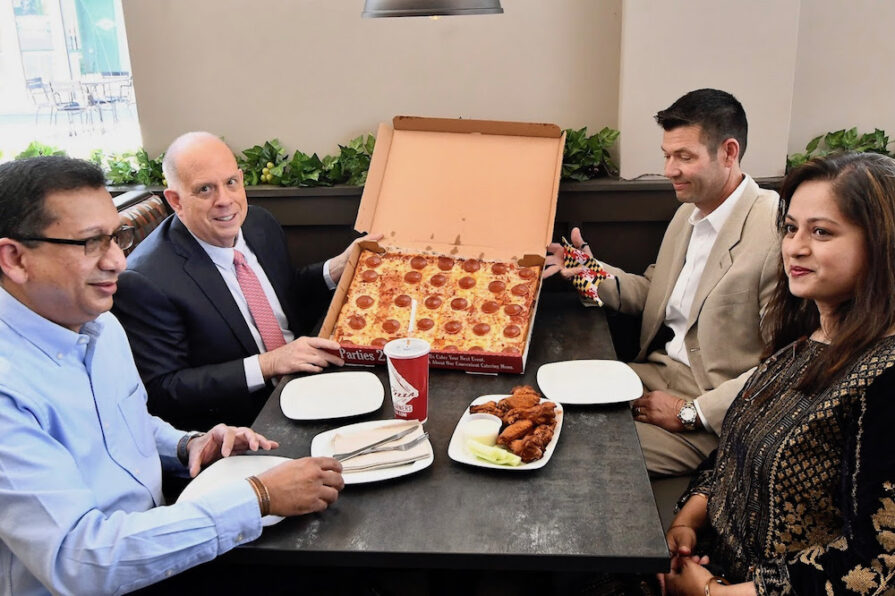 this photo shows Maryland Governor enjoying pizza at Ledo Pizza