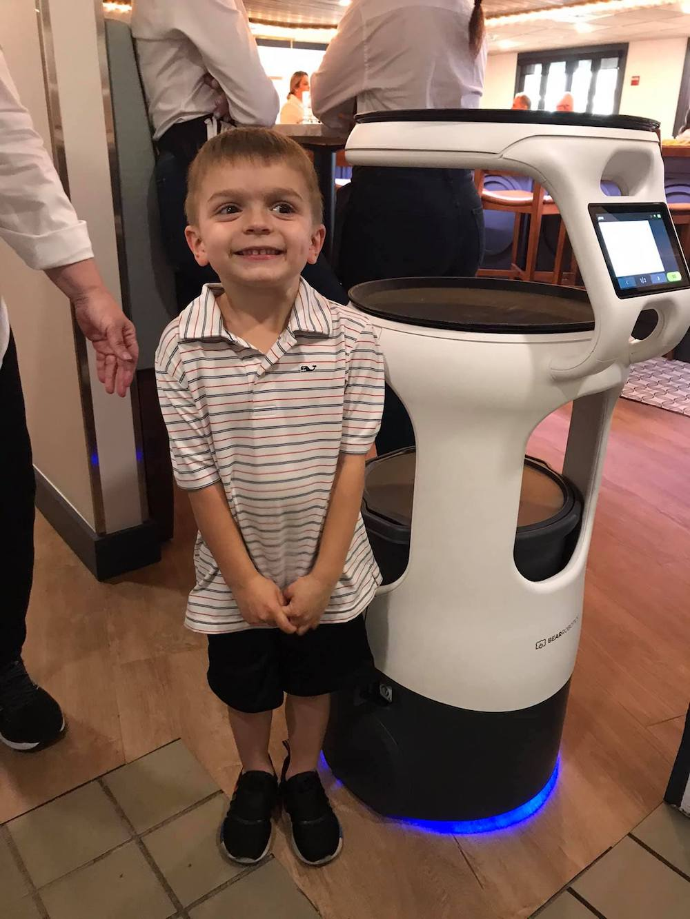 this photo shows a happy little boy standing next to Servie the pizza robot at Angelo's Palace Pizza