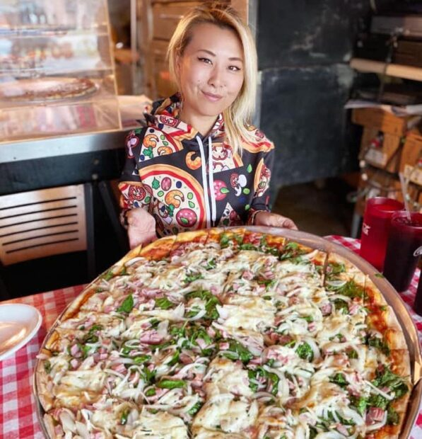 this photo shows competitive eater Raina Huang trying a pizza at Firehouse Pizzeria