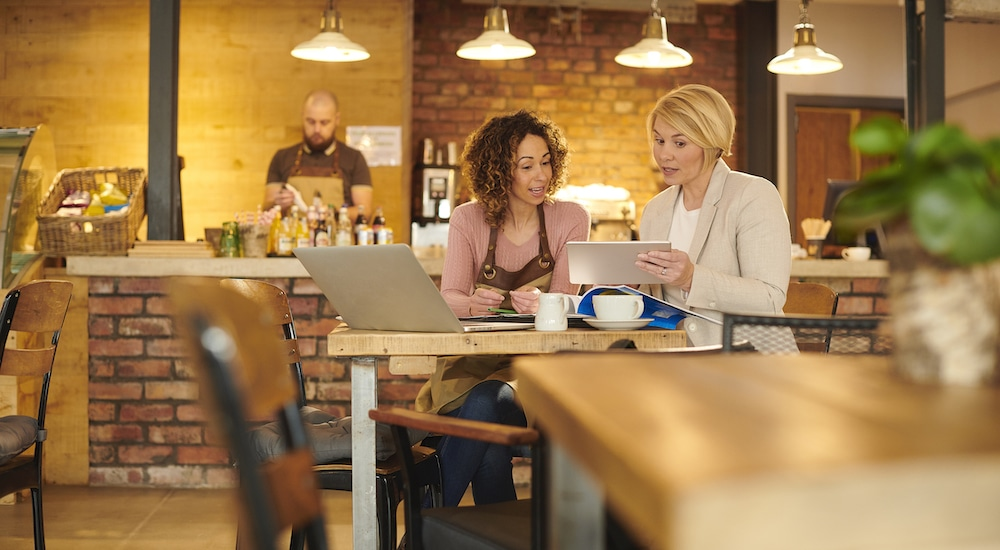 this photo shows a female restaurant owner discussing a loan with a bank representative