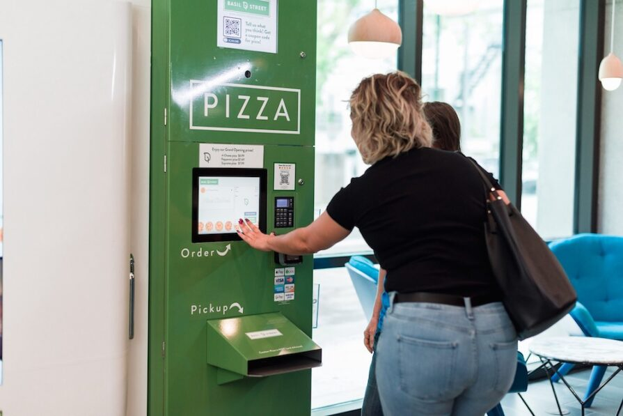 this photo shows a customer trying out one of Basil Street's automated pizza kitchens.