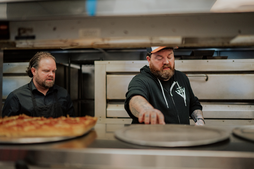 this photo shows the owners of Via 313 making a pizza in the kitchen