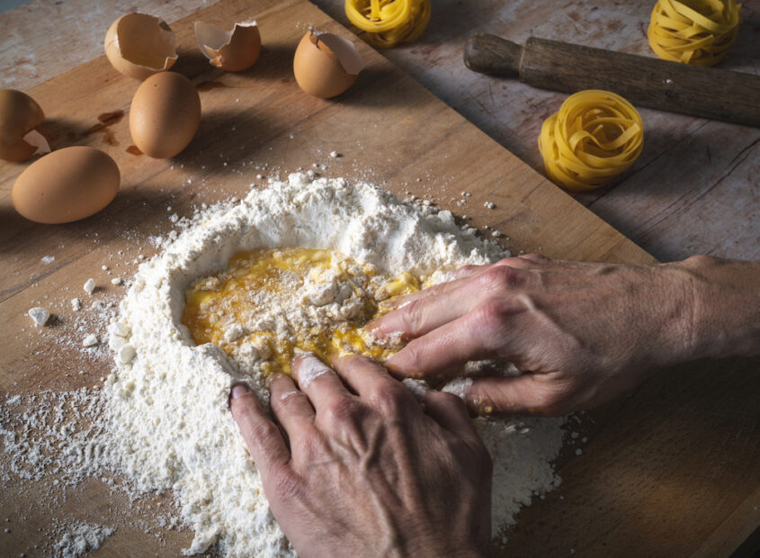 this photo shows eggs being added to pizza dough