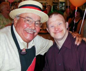 this is a photo of Joe Whitty, founder of Happy Joe's Pizza and Ice Cream Parlor, with a boy who has Down syndrome