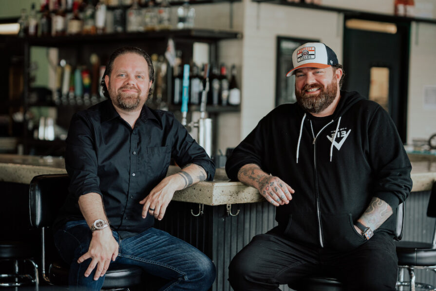 this photo shows Zane and Brandon Hunt, sitting together and smiling in a location of Via 313 pizzeria in Austin, Texas