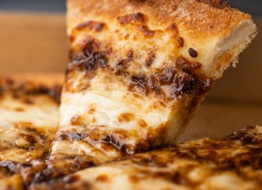 this photo shows a slice of a Vegemite pizza from Domino's Australia