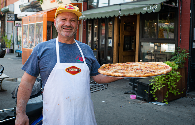 this photo shows Giovanni Fabiano displaying his Vegemite pizza at Rosa's Pizza